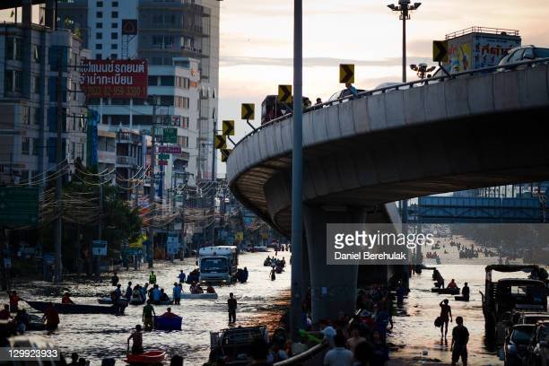 Thai residents make their way through flooded streets on October 22 2011 in Pathum Thani on the outskirts of Bangkok Thailand Hundreds of factories...