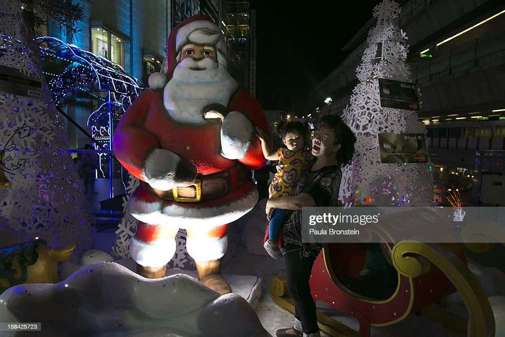 Thai residents pose next to a Santa Claus display in front of the Siam Paragon mall in the shopping district December 16, 2012 in Bangkok,Thailand.Thailand's high tourist season is booming this year compared to 2011 which was tainted by the flooding as Christmas shoppers visit the shopping malls looking for the bargains.