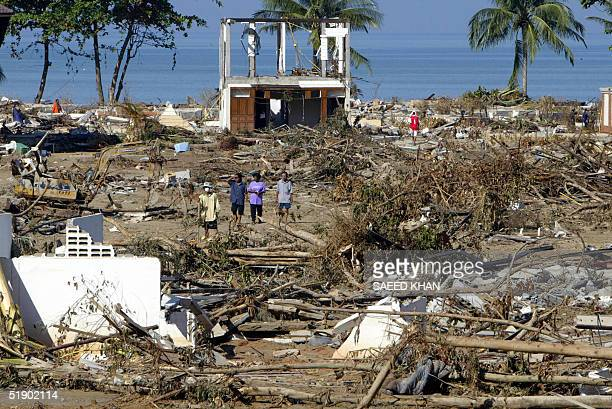 Thai residents walk among debris from the washed away resorts and banglows on the shoreline of Khao Lak beach 30 December 2004 The final death toll...