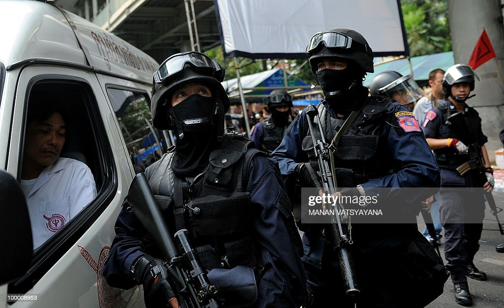 Thai riot policemen stand guard outside the temple inside Red Shirt anti-government protestors in downtown Bangkok on May 20, 2010. The top Thai protest leader urged supporters of the anti-government 'Red Shirt' movement to refrain from violence after riots in the capital, saying 'democracy cannot be built on revenge.'