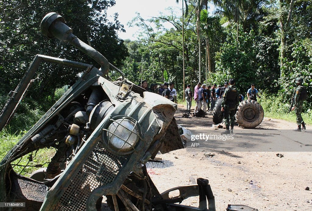 Thai security forces inspect the site of a roadside bomb attack which targeted a military truck transporting soldiers in Thailand's restive southern province of Yala on June 29, 2013. Eight soldiers were killed by the roadside bomb in Thailand's restive south early on June 29, an army spokesman said, raising questions over the durability of a fragile peace process aiming to end the near-decade long insurgency. More than 5,700 people have been killed in a festering insurgency in Thailand's Muslim-majority southern provinces, but optimism for peace has flickered recently after talks between authorities and some rebel groups including the Barisan Revolusi Nasional (BRN). AFP PHOTO