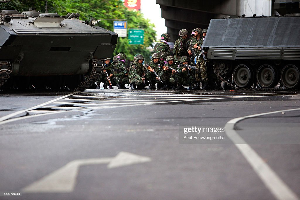 Thai Security forces take cover behind a thai armoured personnel during a clash with protesters on May 19, 2010 in Bangkok, Thailand. Protesters have clashed with military forces for six consecutive days in Bangkok after the government launched an operation to disperse anti-government protesters who have closed parts of the city for more than two months. Despite calls from the United Nations for both sides to begin talks, anti-government protesters in Bangkok have defied orders to leave their fortified camp, with 37 people having died and more than 260 injured since the military began its crackdown.