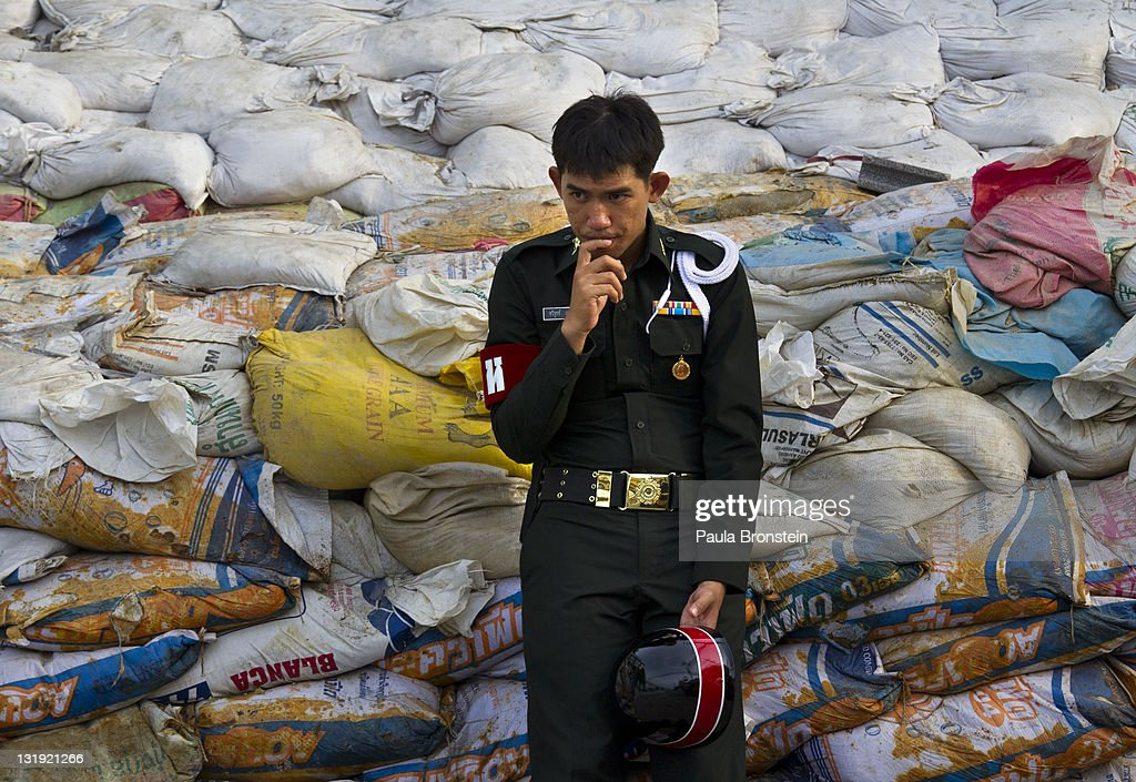 A Thai security guard stands by a wall of sandbags in front of a factory at the Bangchan Industrial Estate area on the outskirts of the capitol city November 8, 2011 in Bangkok, Thailand. Over seven major industrial parks in Bangkok and, thousands of factories have been closed in the central Thai province of Ayutthaya and Nonthaburi with millions of tons of rice damaged. Across the country, the flooding which is now in its third month has affected 25 of Thailand's 64 provinces. Thailand is experiencing the worst flooding in over 50 years which has affected more than nine million people. Over 400 people have died in flood-related incidents since late July according to the Department of Disaster Prevention and Mitigation.