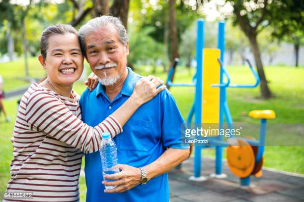 Thai senior couple relaxing after working out at public park in Bangkok