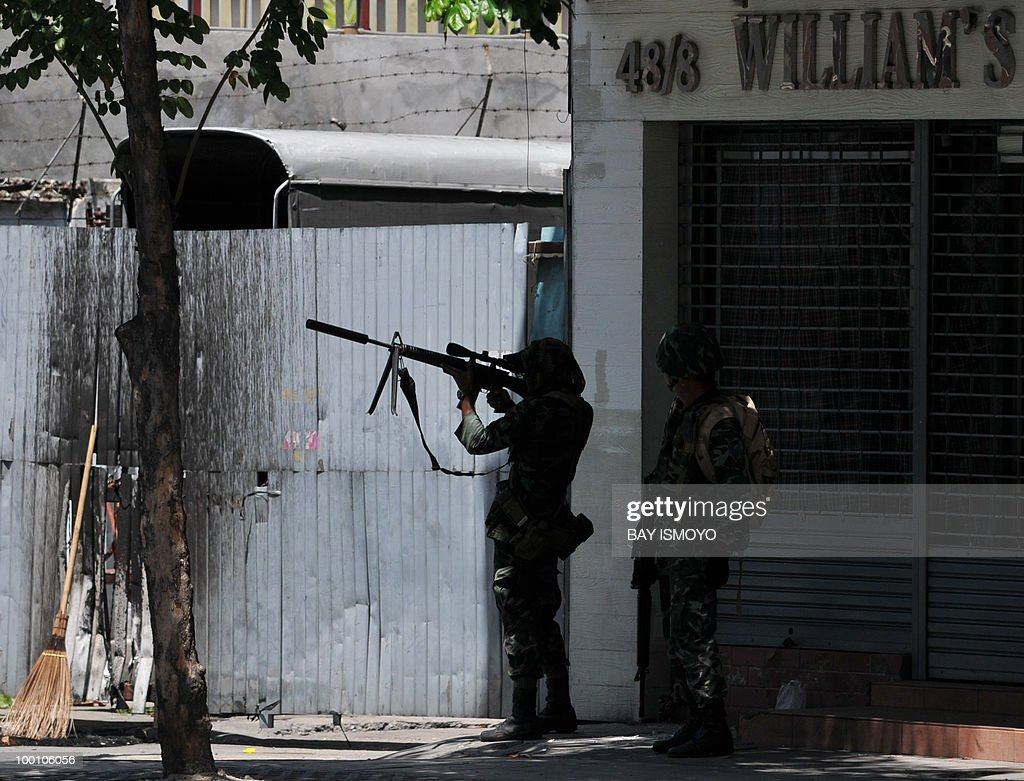 A Thai soldier aims his rifle as they arrive and secure Din Daeng, in Bangkok, on May 21, 2010 after the area was held by the anti-government protesters for several days. Thailand picked up the pieces after violence and mayhem triggered by a crackdown on anti-government protests, as the focus swung to recovery and reconciliation in a divided nation. AFP PHOTO / Bay ISMOYO