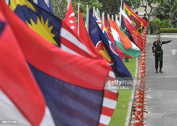 Thai soldier gestures from his position securing a road lined with the flags of member countries of Association of Southeast Asian Nations and...