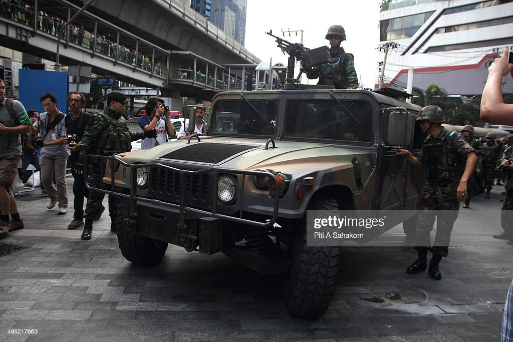 A Thai soldier secures the area with a machine gun outside a shopping mall where protesters gather for an anti-coup demonstration in Bangkok. Hundreds of demonstrators gathered Sunday near a major shopping mall in downtown Bangkok to denounce the country's May 22 coup despite a lockdown by soldiers of some of the city's major intersections. Troops and riot police were stationed in the central shopping district where one political activist had vowed to host a coup party.