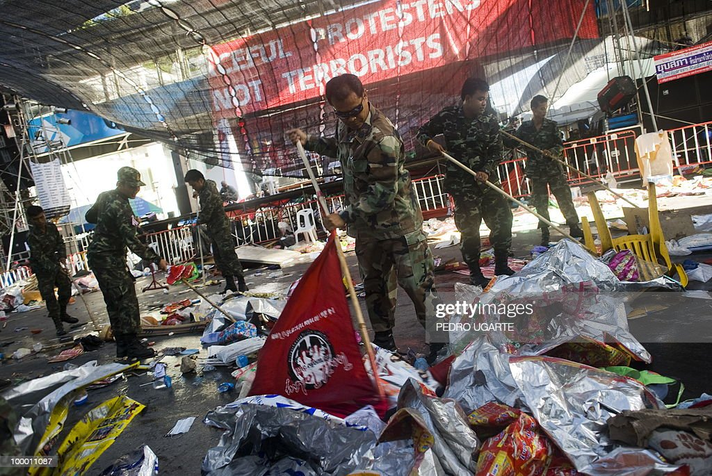A Thai soldier uses a red flag to clean the floor of the main stage used by Red Shirt anti-government protesters in the comercial center of Bangkok on May 20, 2010. Thai troops hunted down militants who went on a rampage of arson and looting in Bangkok, after an army crackdown on their anti-government protest camp that ended two months of street rallies.