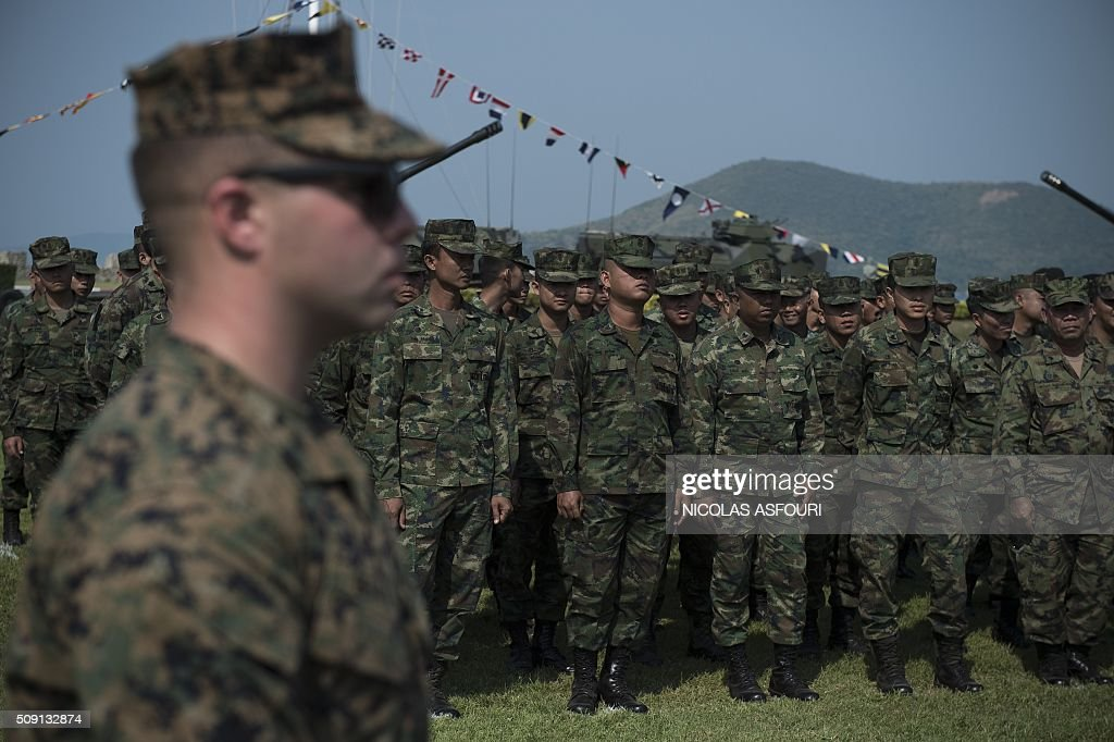 Thai soldiers (back) and a US Marine (L) are seen during the opening ceremony of Cobra Gold 2016 in Sattahip on February 9, 2016. Thailand and the US jointly host Cobra Gold Asia's largest military exercise from February 9 to 20. AFP PHOTO / Nicolas ASFOURI / AFP / NICOLAS ASFOURI