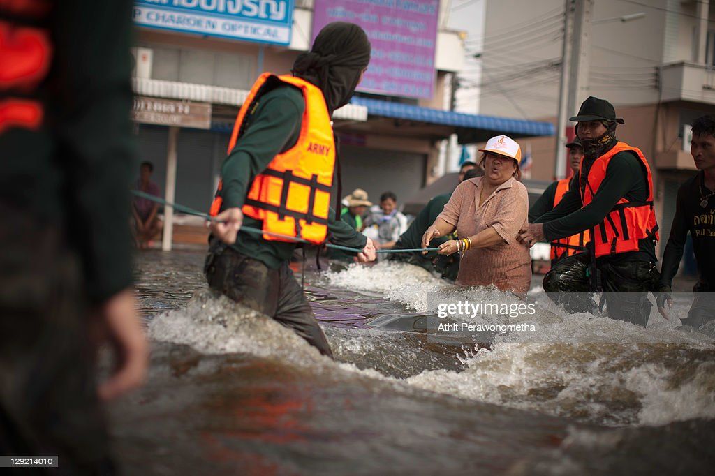 Thai soldiers help residents cross a strong stream of floodwaters as floods continue to hit Pathum Thani province on October 14, 2011 in Pathum Thani, north of Bangkok,Thailand. Crews of public workers, soldiers and volunteers are evacuating residents from flooded areas north of Bangkok as efforts continue to protect the capital from existing floodwaters combined with increased rainfall and rising tides during the worst floods to hit the country for decades.