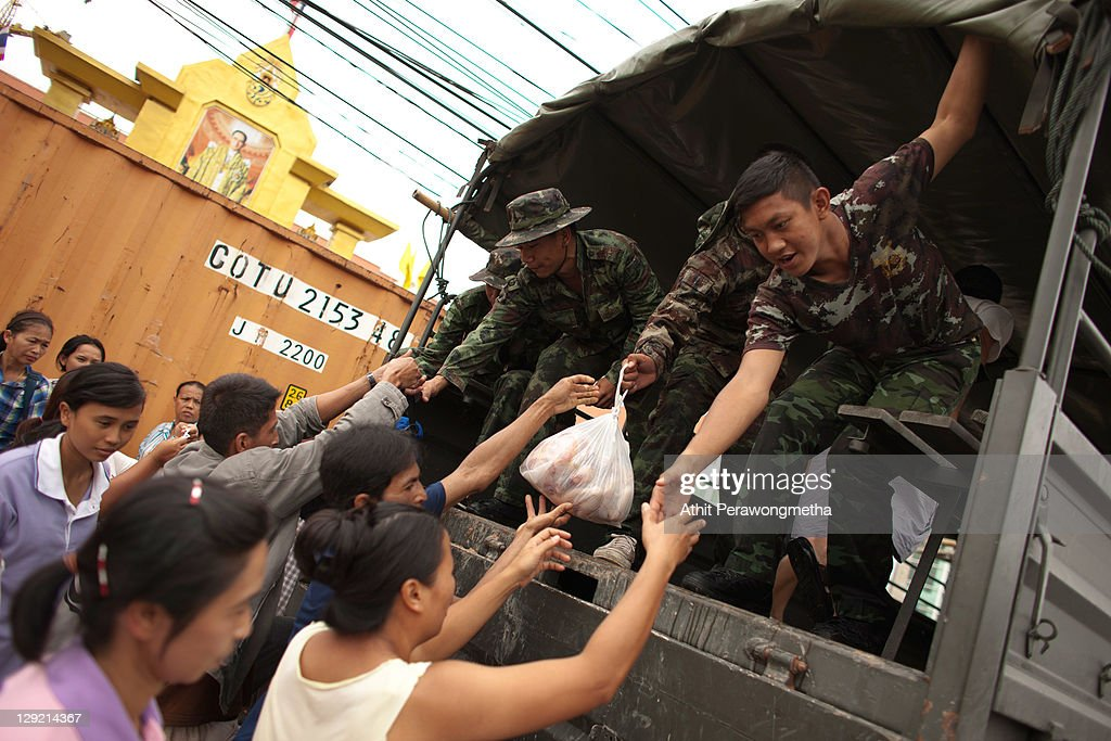 Thai soldiers help residents onto a military truck as floods continue to hit Pathum Thani province on October 14, 2011 in Pathum Thani, north of Bangkok,Thailand. Crews of public workers, soldiers and volunteers are evacuating residents from flooded areas north of Bangkok as efforts continue to protect the capital from increased rainfall and rising tides during the worst floods to hit the country for decades.
