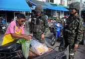 Thai soldiers perform a security check on a villager at a market in Thailand's restive southern province of Narathiwat on January 3 2014 Stuttering...