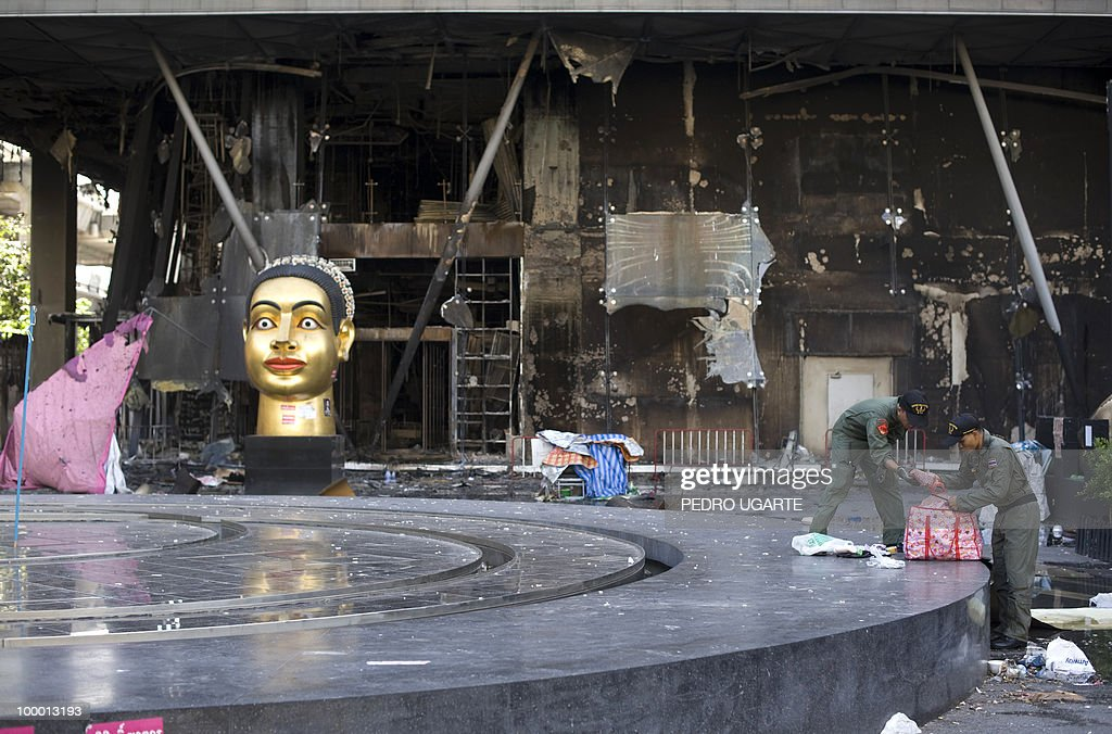 Thai soldiers search a bag in front of Thailand's biggest shopping mall - Central World - after it was set ablaze the day before following an army assault on an anti-government protest site in downtown Bangkok on May 20, 2010.Thai troops hunted for militant protesters who left parts of Bangkok in flames as the authorities extended a night curfew in the capital despite tentative signs of a return to normality.