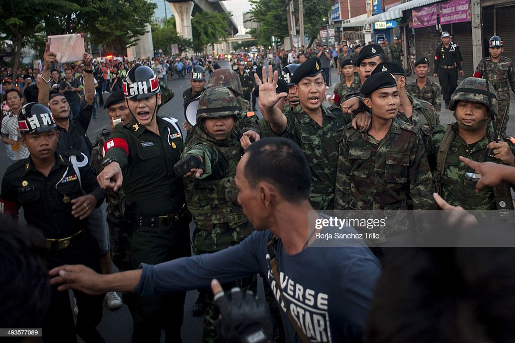 Thai soldiers shout at anti-coup protesters to maintain order during a demostrations at Victory Monument on May 24, 2014 in Bangkok, Thailand. Anti-coup protesters continue gathering in central Bangkok two days after the bloodless coup d'etat. Thailand's military Junta detained yesterday former premier Yingluck Shinawatra and ordered more than 135 politicians and prominent academics to come to the military council to report to them. Curfew remains from 11pm to 4am and Martial law bans public assembly.