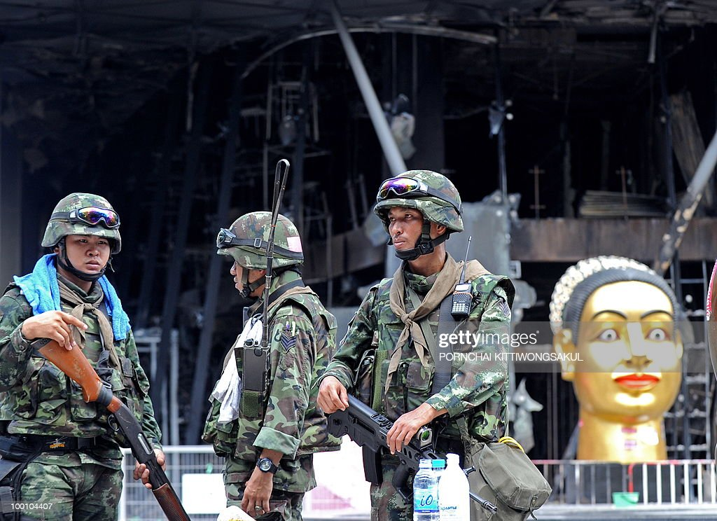 Thai soldiers stand guard in front of Thailand's biggest shopping mall - Central World - after it was set ablaze from anti-government protesters in Bangkok on May 21, 2010. Thailand picked up the pieces after violence and mayhem triggered by a crackdown on anti-government protests, as the focus swung to recovery and reconciliation in a divided nation.