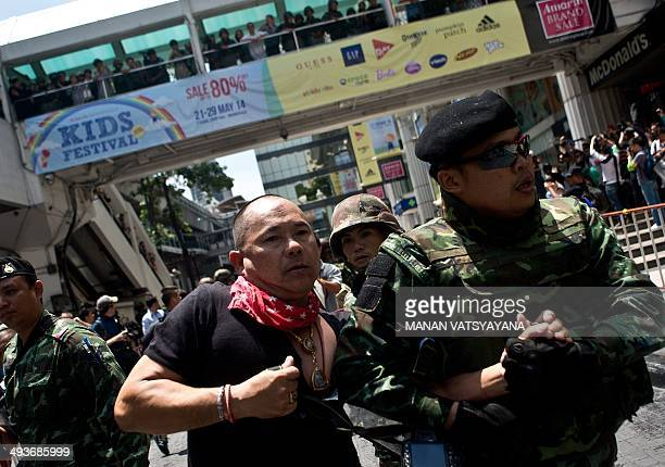 Thai soldiers take away an alleged RedShirt protester ahead of a planned gathering in Bangkok on May 25 2014 Thailand's military junta said it had...