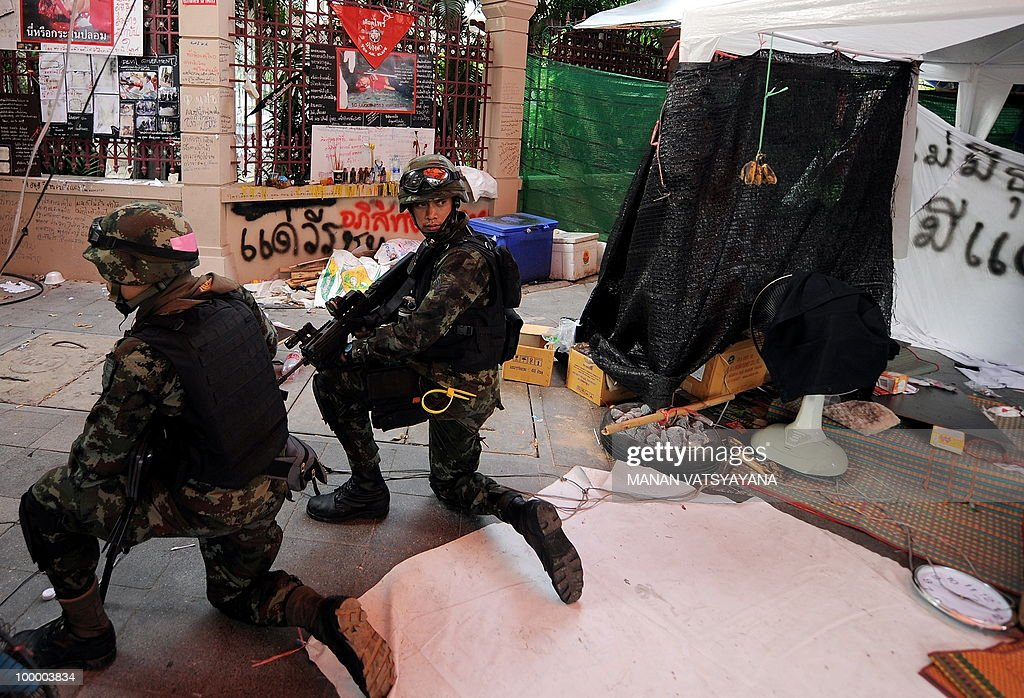 Thai soldiers take positions after hearing gunshots inside the Red Shirt anti-government protesters camp in Bangkok on May 20, 2010. Plumes of smoke hung overhead and gunfire crackled as Bangkok emerged from an curfew aimed at quelling mayhem unleashed by enraged anti-government protesters targeted in an army offensive.