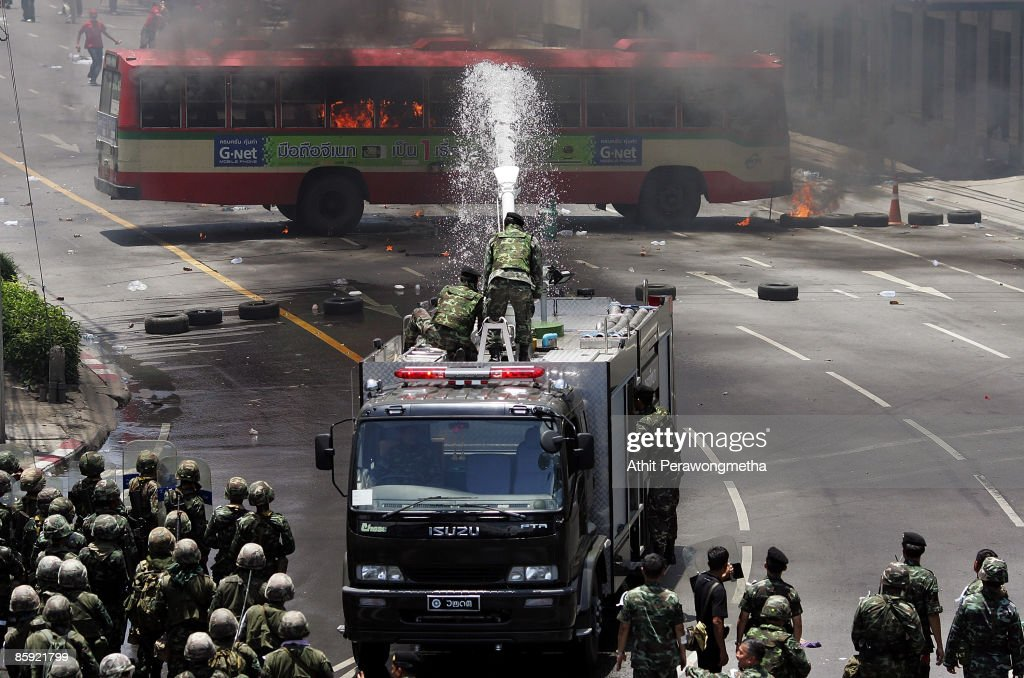 Thai soldiers use water cannons to extinguish flames on a bus torched by supporters of former prime minister Thaksin Shinawatra near Victory Monument on April 13, 2009 in Bangkok, Thailand. Prime Minister Abhisit has called for calm as clashes between the Thai army and anti government protestors have escalated, resulting in reports of the army having fired live rounds over the heads and into crowds of demonstrators.