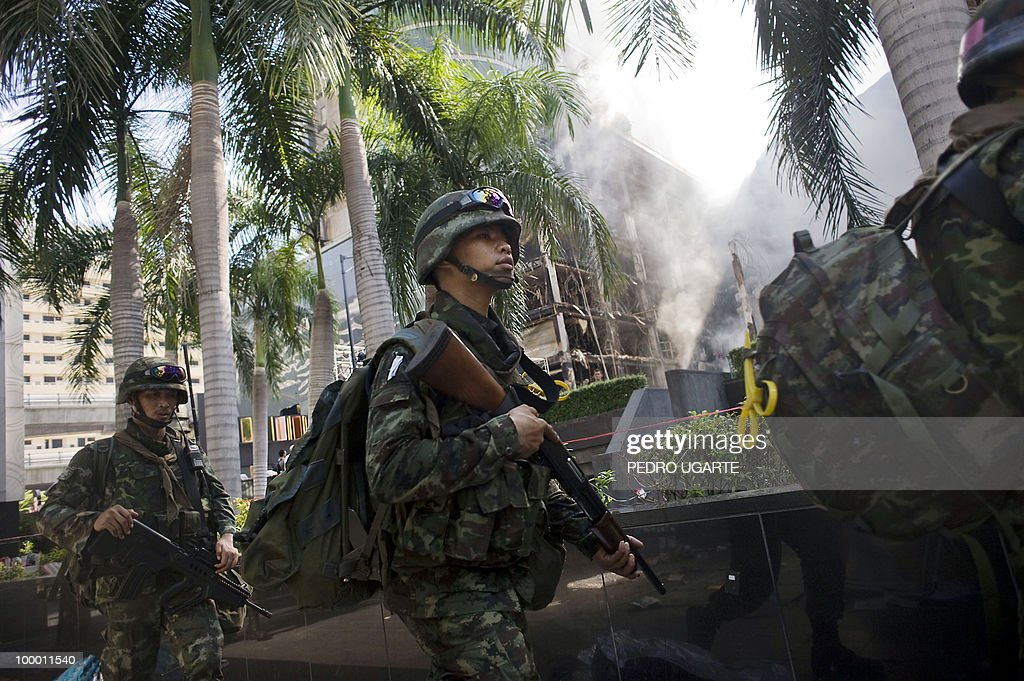 Thai soldiers walk past a shopping mall set on fire by Red Shirt anti-government protesters after a goverment crackdownd in the commercial center of Bangkok on May 20, 2010. Thai troops hunted down militants who went on a rampage of arson and looting in Bangkok, after an army crackdown on their anti-government protest camp that ended two months of street rallies.