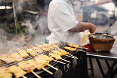 Thai Street Vendor Grilling Pork
