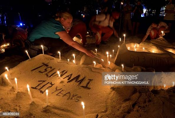 Thai students and foreign tourists place candles on a sand sculpture during commemorations on the the tenth anniversary of the 2004 tsunami at Patong...