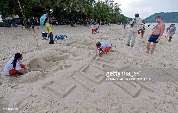 Thai students make sand sculptures during the tenth anniversary of the 2004 tsunami at Patong beach in Phuket province on December 26 2014 Prayer...