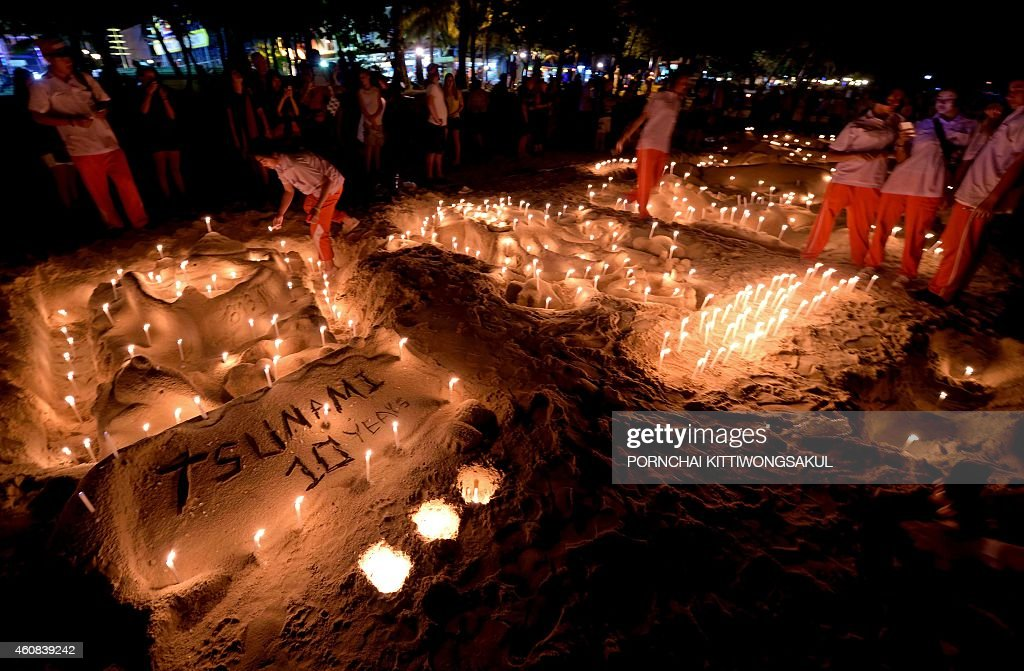 Thai students place candles on a sand sculpture during commemorations on the the tenth anniversary of the 2004 tsunami at Patong beach in Phuket...
