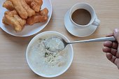 thai style breakfast ,rice porridge, coffee and chinese bread stick on wooden table