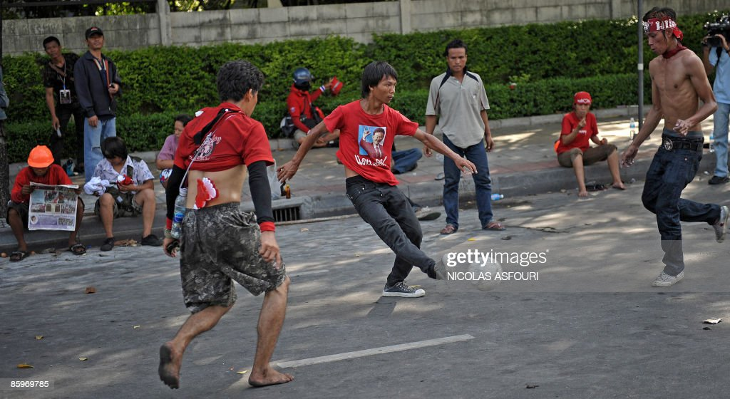 Thai supporters of ex-Prime Minister Thaksin Shinawatra play football near the Governement house, in Bangkok on April 14, 2009. Anti-government protesters massed outside the Thai premier's offices in Bangkok said that they would disperse as troops backed up by armoured vehicles tightened their grip on the city.