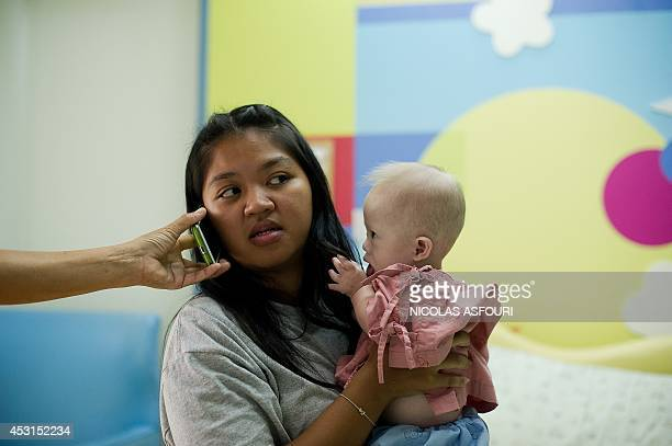 Thai surrogate mother Pattaramon Chanbua holds her baby Gammy born with Down Syndrome as a relative holds up a mobile phone to her ear at the...