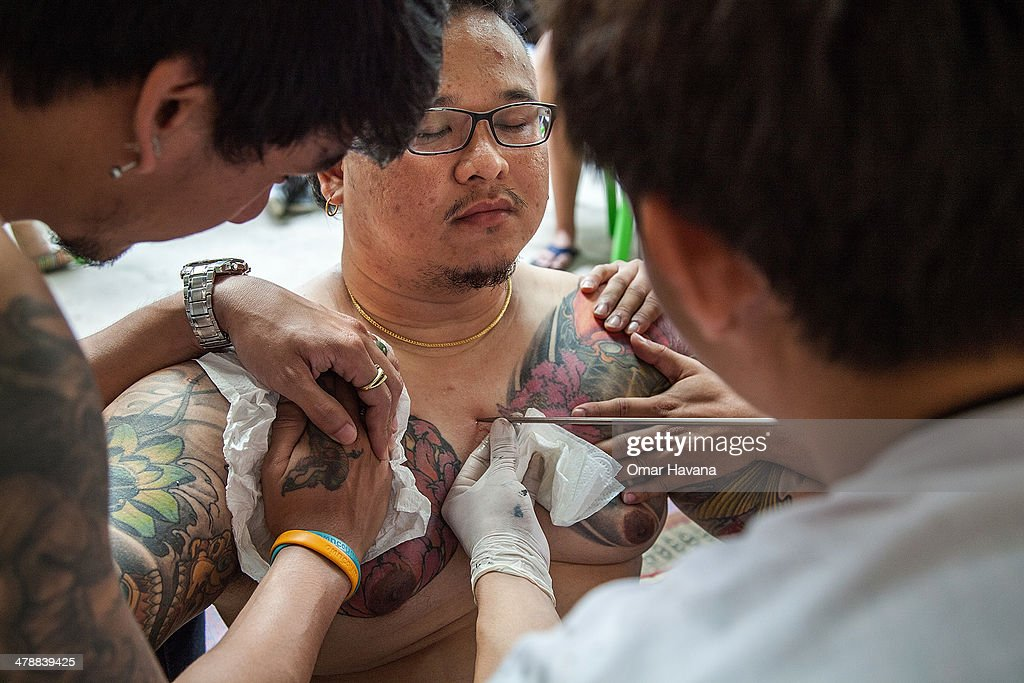 Thai tattoo master carves a tattoo on a devotee's chest with a long needle during the celebration of the annual Tattoo festival at Wat Bang Phra on...