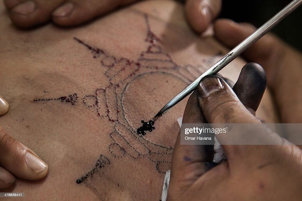 Thai tattoo master carves a tattoo on a foreigner devotee's back with a long needle during the celebration of the annual Tattoo festival at Wat Bang...