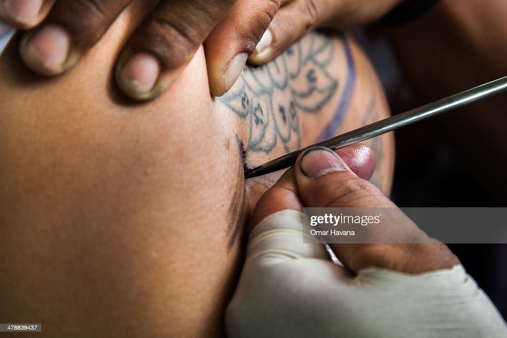 Thai tattoo monk master carves a tattoo on a devotee's back with a long needle during the celebration of the annual Tattoo festival at Wat Bang Phra...