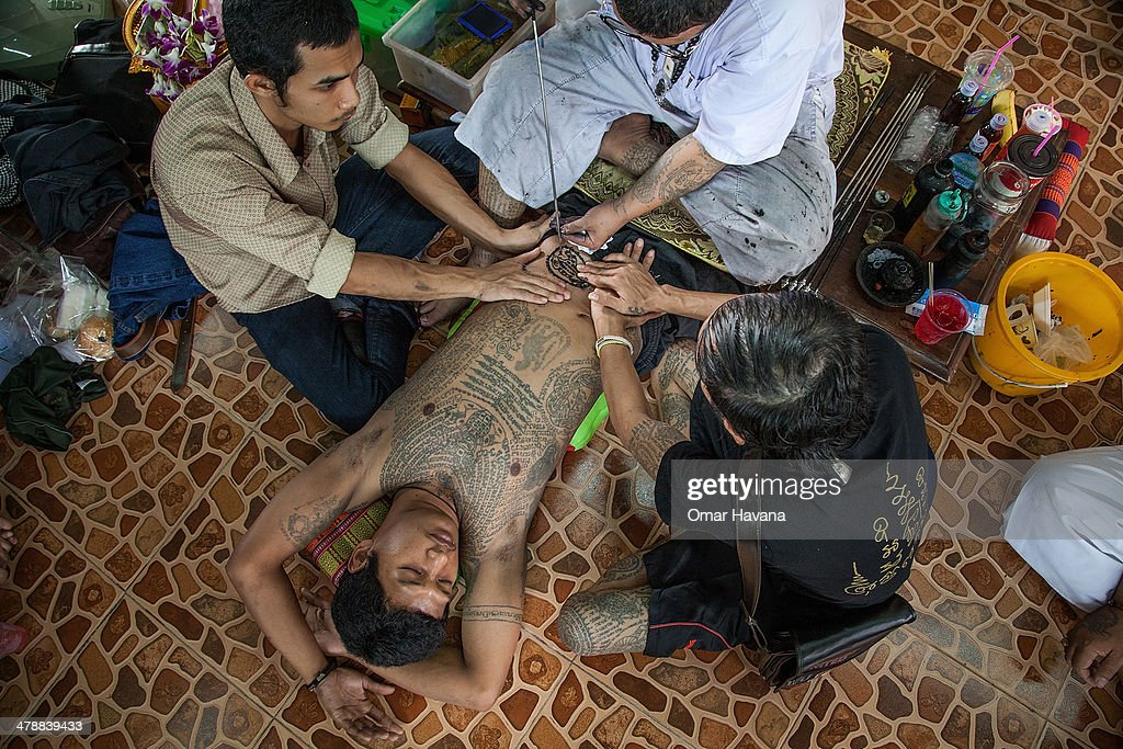 Thai tattoo monk master carves a tattoo on a devotee's belly with a long needle during the celebration of the annual Tattoo festival at Wat Bang Phra...