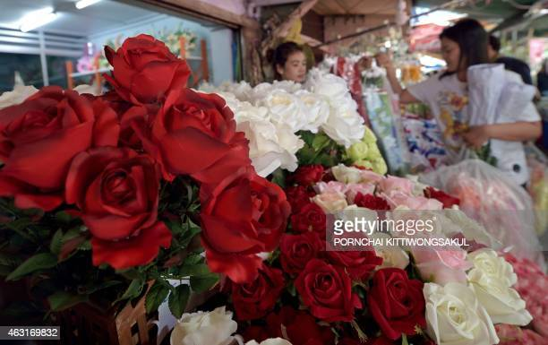 A Thai teenager selects a bouquet of roses ahead of Valentine's day at a flower market in Bangkok on February 11 2015 People are expected to spend...