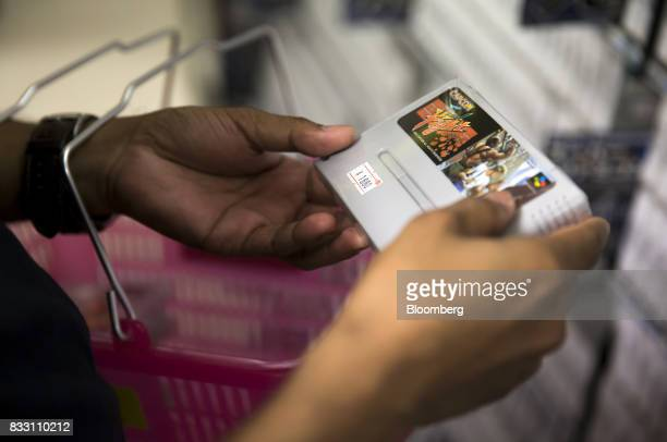 A Thai tourist looks at a video game cartridge for the Nintendo Co Super Nintendo Entertainment System console at the Super Potato video game store...