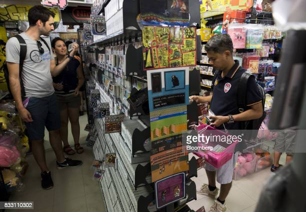 A Thai tourist right shops for video games for the Nintendo Co Super Nintendo Entertainment System console at the Super Potato video game store in...