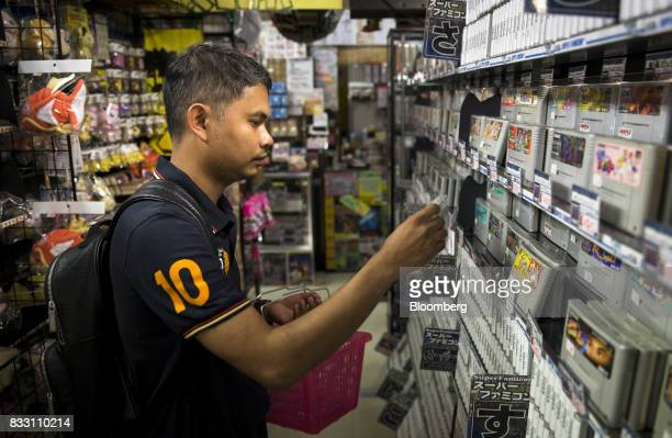 A Thai tourist shops for video games for the Nintendo Co Super Nintendo Entertainment System console at the Super Potato video game store in the...