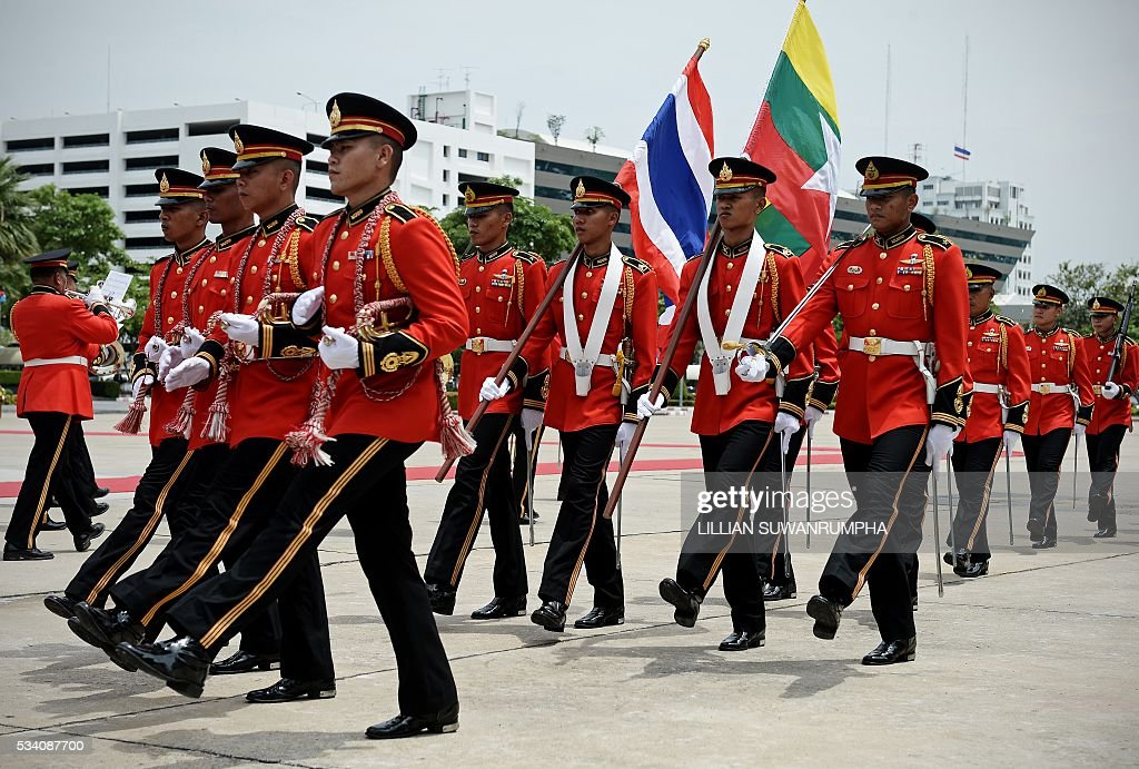 Thai troops march with Thai and Burmese flags before the arrival of Myanmar army chief General Min Aung Hlang in Bangkok on May 25, 2016. The Burmese general is on a three day visit to Thailand and is scheduled to meet senior officials including Thailand's military ruler General Prayuth Chan-Ocha. / AFP / LILLIAN