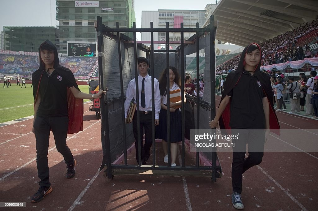 Thai university students are seen inside a mock prison cell as they participate in a parade lampooning the military junta during a varsity football match at the National stadium in Bangkok on February 13, 2016. Thai university students lampooned the military at a varsity football game in a rare act of open defiance against the junta that has strangled political expression since toppling an elected government two years ago. AFP PHOTO / Nicolas ASFOURI / AFP / NICOLAS ASFOURI