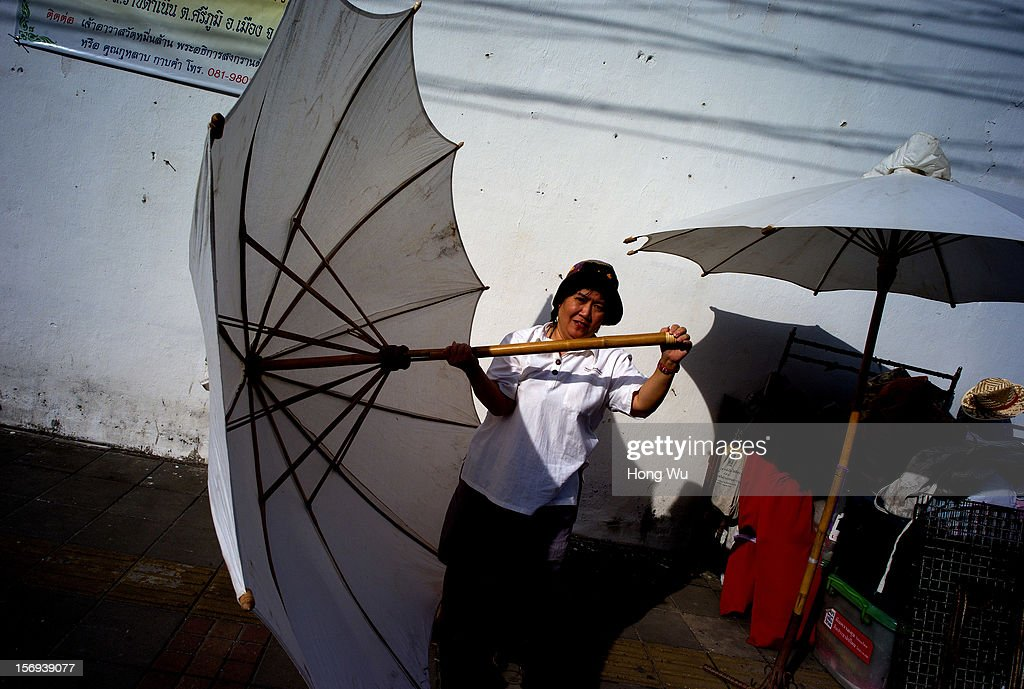 Thai vendor holds an umbrella as she sets up her stall at Chiang Mai Sunday Market on November 25, 2012 in Chiang Mai, Thailand. The Chiang Mai Sunday Market, also called walking Street Market, is held from 4:00 pm until midnight and starts at Thapae Gate, running along the length of Ratchadamnoen Road through the heart of the Old City and is a Chiang Mai institution. Many of the stallholders have personally made the items they sell and the many hand crafted objects are a testimony to the skills and inventiveness of local people, which attracts local citizens and foreign tourists.
