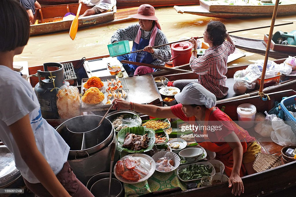 Thai vendors prepare food with fresh sea food, meat and vegetables on their boats while stationed on the bank of the canal in floating market on October 13 in Damnoen Saduak, Thailand. Damnoen Saduak is a district in the province of Ratchaburi in central Thailand. The central town has become a tourist attraction with its famous floating market.