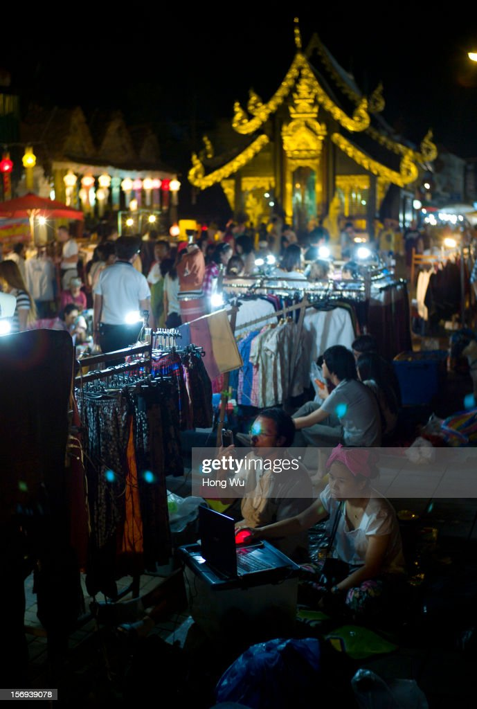Thai vendors wait for customers at Chiang Mai Sunday Market on November 25, 2012 in Chiang Mai, Thailand. The Chiang Mai Sunday Market, also called walking Street Market, is held from 4:00 pm until midnight and starts at Thapae Gate, running along the length of Ratchadamnoen Road through the heart of the Old City and is a Chiang Mai institution. Many of the stallholders have personally made the items they sell and the many hand crafted objects are a testimony to the skills and inventiveness of local people, which attracts local citizens and foreign tourists.