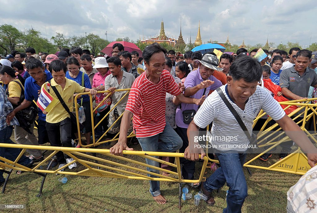 Thai villagers break through barriers to collect rice seeds during the annual Royal Ploughing Ceremony, which marks the traditional beginning of the rice-growing season, at Sanam Luang in Bangkok on May 13, 2013. Based on what sacred oxen ate at the ceremony, court astrologers and seers predicted a good harvest, an abundance of food and plentiful water. AFP PHOTO / PORNCHAI KITTIWONGSAKUL
