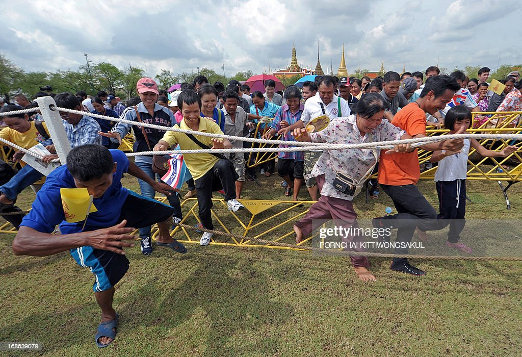 Thai villagers break through barriers to collect rice seeds during the annual Royal Ploughing Ceremony, which marks the traditional beginning of the rice-growing season, at Sanam Luang in Bangkok on May 13, 2013. Based on what sacred oxen ate at the ceremony, court astrologers and seers predicted a good harvest, an abundance of food and plentiful water.