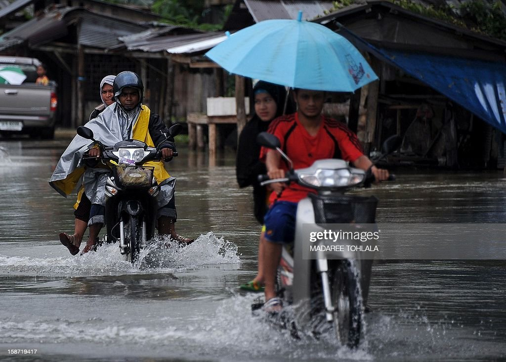 Thai villagers ride motorcycles through flood waters after flash floods hit parts of Thailand's restive southern province of Narathiwat on December 26, 2012. Southern provinces of Thailand have been hit by floods over the past few days, with tens of thousands of residents affected.