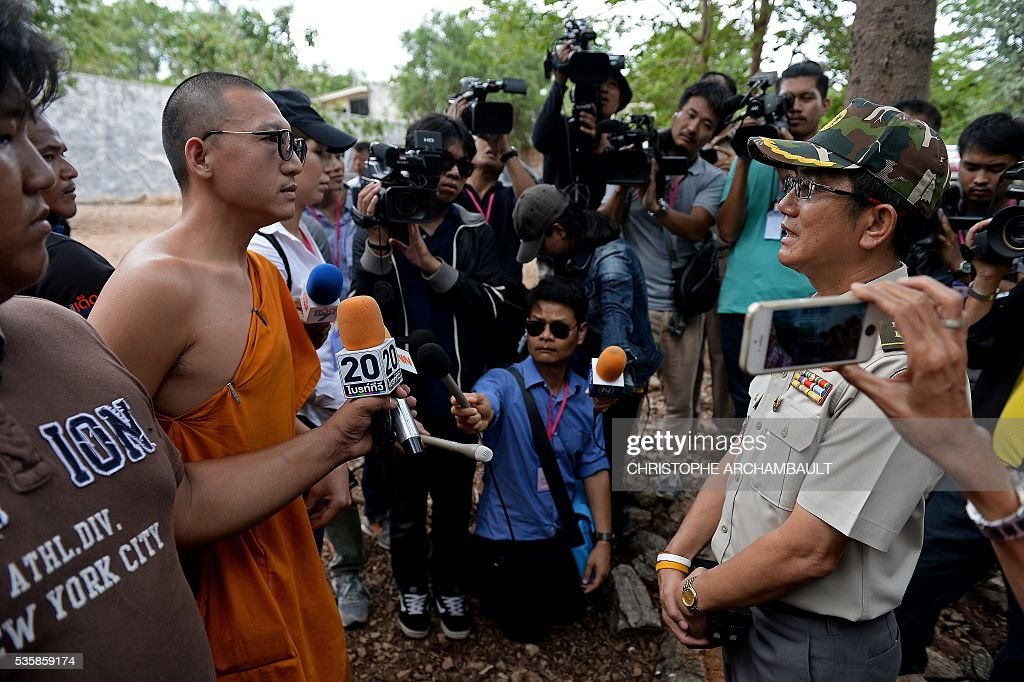 A Thai wildlife official speaks with a monk before officials removed tigers from enclosures at the Wat Pha Luang Ta Bua Tiger Temple in Kanchanaburi province, western Thailand on May 30, 2016. Thai wildlife officials armed with a court order on May 30 resumed the treacherous process of moving tigers from a controversial temple which draws tourists as a petting zoo, but stands accused of selling off the big cats for slaughter. / AFP / CHRISTOPHE