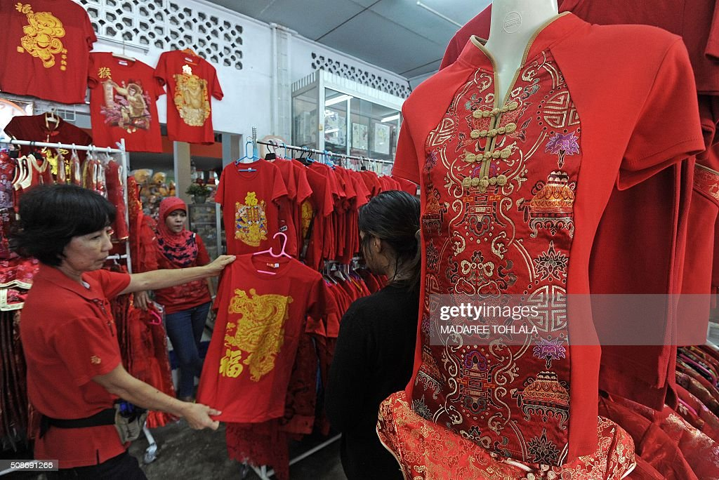 A Thai woman buys a T-shirt at a shop ahead of the Lunar New Year in Thailand's southern Narathiwat province on February 6, 2016. The Lunar New Year which falls on February 8 will mark the start of the year of the monkey and will be widely celebrated throughout the country where 14 percent of the population is ethnic Chinese. AFP PHOTO / Madaree TOHLALA / AFP / MADAREE TOHLALA