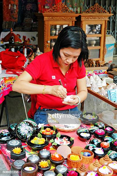 Thai woman carving flowers in piece of soap