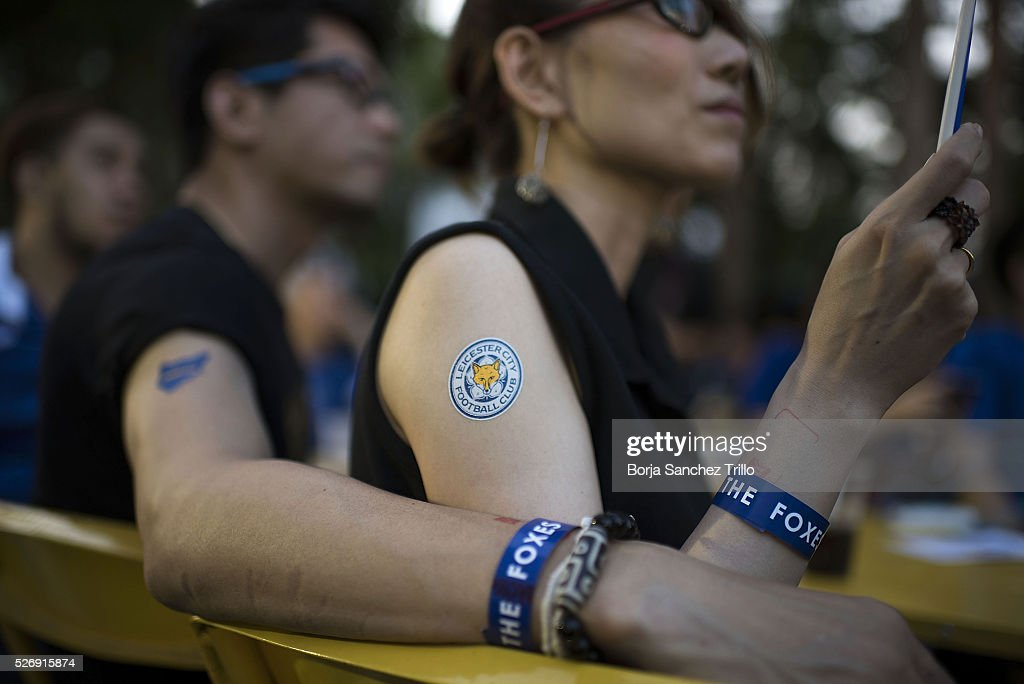 A Thai woman holds a Leicester City flag while watching her team plays against Manchester United on May 1, 2016 in Bangkok, Thailand. Leicester City fans gather at King Power Hotel in Bangkok to watch the Premier League game between Manchester United and Leicester City at Old Trafford.